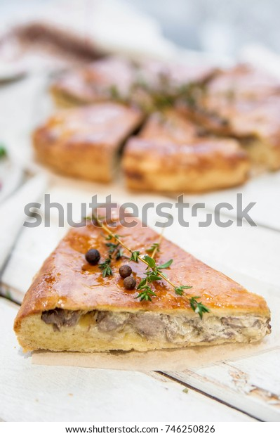 Mushroom pie piece on a wooden rustic background