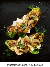 Mushroom sandwich, open faced sandwich with addition of brown sliced mushrooms, camembert cheese, lettuce and fresh parsley on a black background, top view