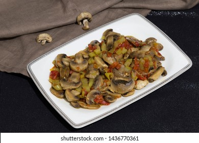 mushroom saute with pepper and tomatoes and olive oil in the white plate on the black background.
