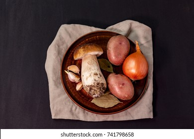 Mushroom with a set of vegetables on a plate on a dark background