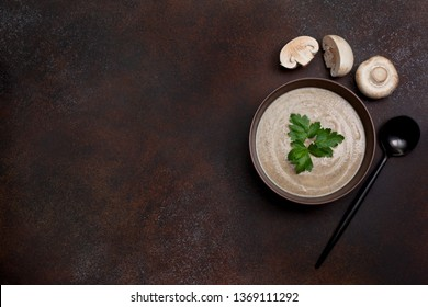 mushroom soup in a brown bowl, champignons on a brown background. view from above. copy space