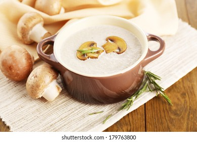 Mushroom soup in pot, on wooden background
