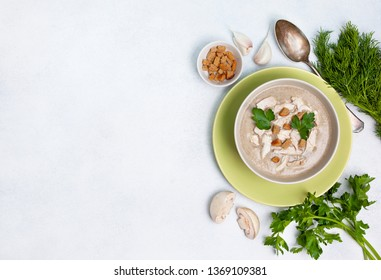 mushroom soup in a white bowl, champignons, croutons, fresh greens on a white background. view from above. copy space