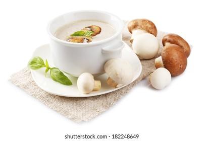 Mushroom soup in white bowl, on napkin, isolated on white
