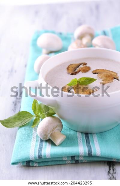 Mushroom soup in white pot, on napkin,  on wooden background