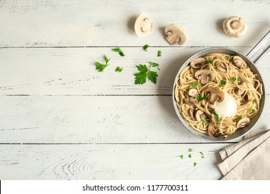 Mushroom Spaghetti Pasta and cream sauce on white background, top view. Homemade italian pasta with champignon mushroom in cooking pan.