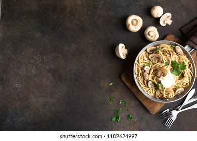 Mushroom Spaghetti Pasta and cream sauce on rustic background, top view, copy space. Homemade italian pasta with champignon mushroom in cooking pan.