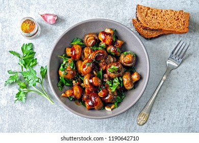 Mushrooms in a bowl, cooked in soy sauce with parsley and garlic. Vegan bowl with mushrooms. Healthy vegan lunch.