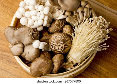 Mushrooms Fresh Organic, enoki, shiitaki, hen of the woods, baby portabello, button mushrooms in wooden woven basket at a restaurant. Variety of Mushrooms in a basket, closeup and shot overhead.
