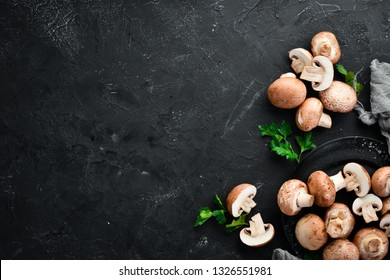 Mushrooms on a black stone background. Champignons Top view. Free copy space.