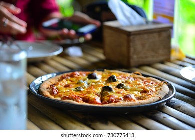 Mushrooms pizza in plate on bamboo table.