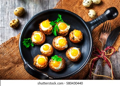 Mushrooms with quail eggs. Mushrooms on black pan. Quail eggs and cutlery close. Selective focus