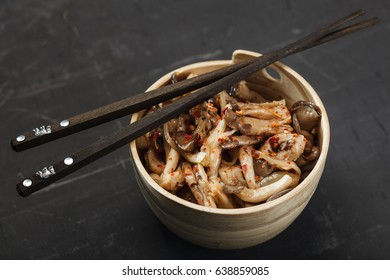 Mushrooms salad in wooden bowl and chopsticks