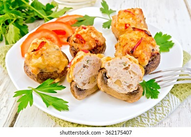 Mushrooms stuffed with meat whole and sliced, parsley and tomatoes in a white plate on a napkin, fork on the background of wooden boards