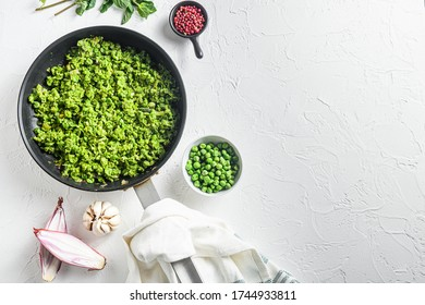 Mushy peas recipe cooked frying pan and peas in bowl with mint shallot pepper and salt over white stone surface organic keto food top view lat flay overhead photo space for text