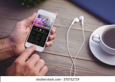 Music app against person holding smart phone at desk
