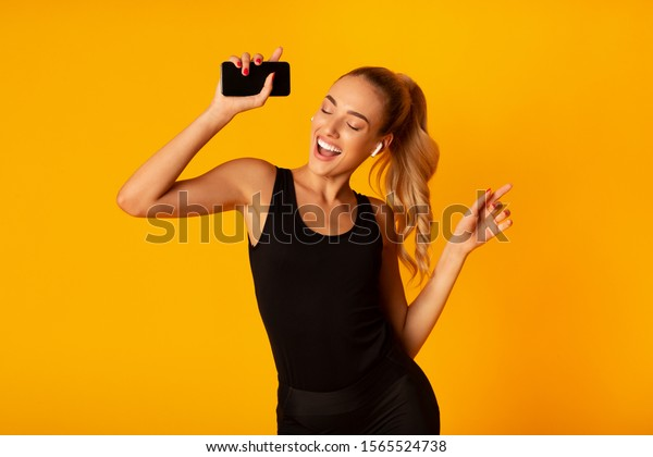 Music App. Sporty Woman In Wireless Earbuds Holding Smartphone And Dancing Over Yellow Background. Studio Shot