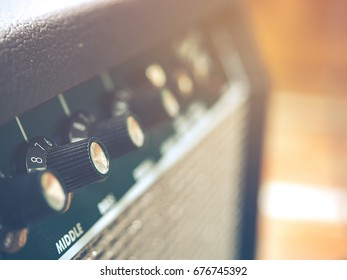 Music audio system concept.Grunge black volume control knob of vintage amplifier or button control in recording room. Vintage retro style and blur light bokeh for copy space. Selective focus.
