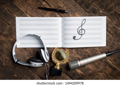 Music award concept background. Musical book with a treble clef, golden medal award trophy, microphone and headphones on wooden table.