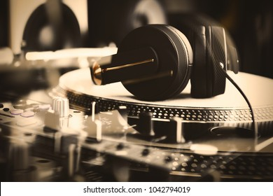 Music background.Concert DJ headphones on vinyl turntable player.Professional disc jockey audio equipment for nightclub parties.scratch vinyl records & listen to the music in high quality