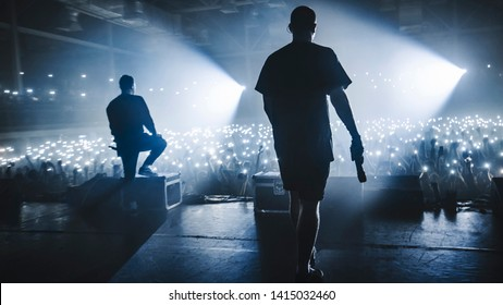 Music band group silhouette perform on a concert stage.   audience holding cigarette lighters and mobile phones
