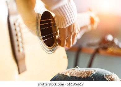 Music, close-up. Musician with a wooden guitar
