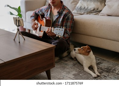 Music college hipster student practicing acoustic guitar exercise, reading notes from phone on tripod. Man taking an online musical courses at home during quarantine. Background, close up