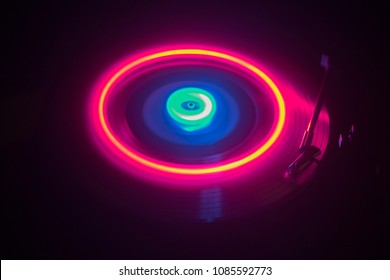 Music concept. Freezelight glowing vinyl on dark background or Turntable playing vinyl with glowing abstract lines concept on dark background. For Club poster Design