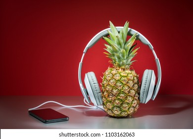 Music concept, pineapple with headphones, red background