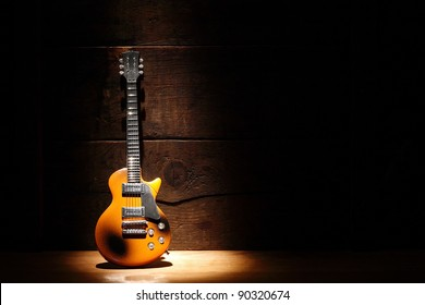 Music concept.Electric guitar standing near wooden wall under beam of light