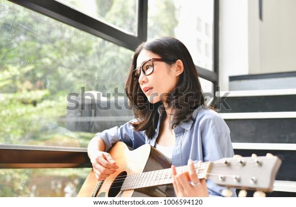 音楽のコンセプト。ギターを弾くアジア人の女の子。音楽にくつろぐアジアの女性。アジアの女性は幸せな生活を送る。家でギターを弾く美しいアジア人の女の子。