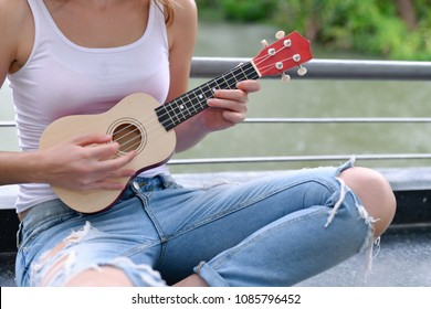 Music Concepts. beautiful girls playing Ukulele. women relaxing with music.  women have a happy lifestyle. Beautiful girl playing ukulele in the rain garden.