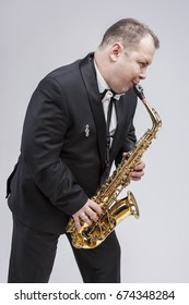 Music Concepts. Portrait of Caucasian Mature Expressive Saxophone Player Posing in Suit Against White Background. Vertical Image