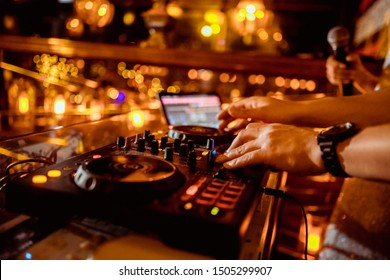 music controller DJ in the booth on the background of the dance floor with dancing people at the party
