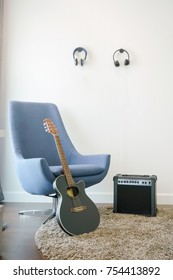 Music corner in the living room with retro style armchair, headphones and guitar