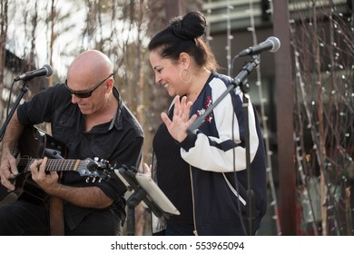 Music Duo singing and playing guitar at an outdoor venue