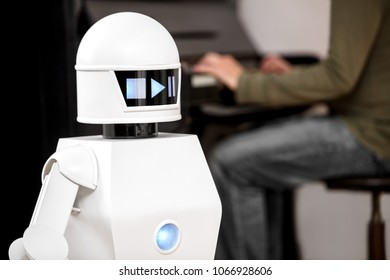 music entertainment service robot is playing music files while a man in the background is playing a piano.