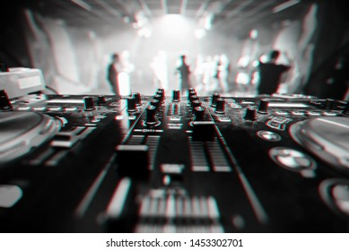 music equipment DJ in a nightclub closeup with blurred background dancing people. Black and white photo with glitch effect and small grain