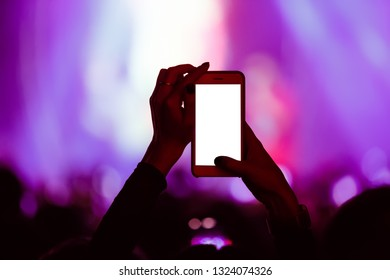 Music fan girl filming pop music concert in nightclub with smartphone camera.Empty white screen for text.Young girl silhouette with mobile phone on dance floor in the club