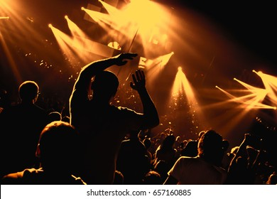 Music Fest. A man dancing in a crowd at a music concert. Light show in a music hall.