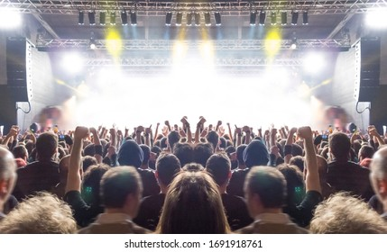 Music festival crowd,concert spectators in front of a bright stage with live music