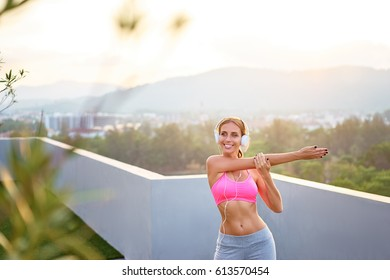 Music and fitness. Young woman in sports wear with headphones stretching outdoors.