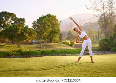 Music and fitness. Young woman in sports wear with headphones exercising in park.