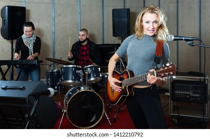 Music garage band with passionate emotional woman vocalist and guitarist playing in recording music studio