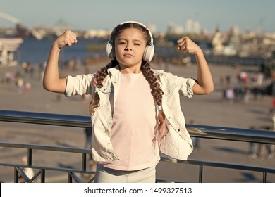 Music has healing power. Adorable child enjoy music playing in earphones on urban background. Little girl enjoying her favorite music outdoor. Cute small kid listening to energetic music in headset.