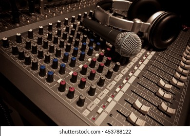 Music instruments or dj concept.the microphone and headphones on sound mixer background.