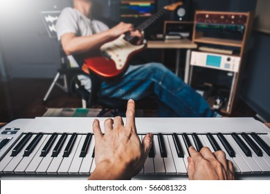music jamming in sound studio, pianist hands playing keyboard on blurred guitar player background. film filter
