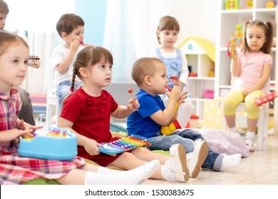 Music lesson for group of children in kindergarten or kids centre