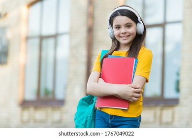 Music lesson. Little child hold books for private lesson. School lesson. Engish learner wear headphones. Listening comprehension skills. Take your lesson anytime and anywhere.