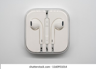 Music Listening Device. Bangkok, Thailand - Aug 21, 2018: Apple Air Pods White Headphones with case isolated on white background.